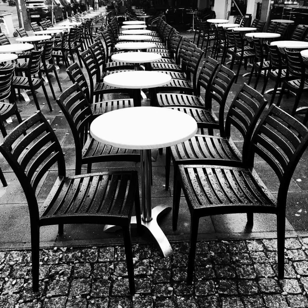 Stühle vor einer Kneipe im Regen